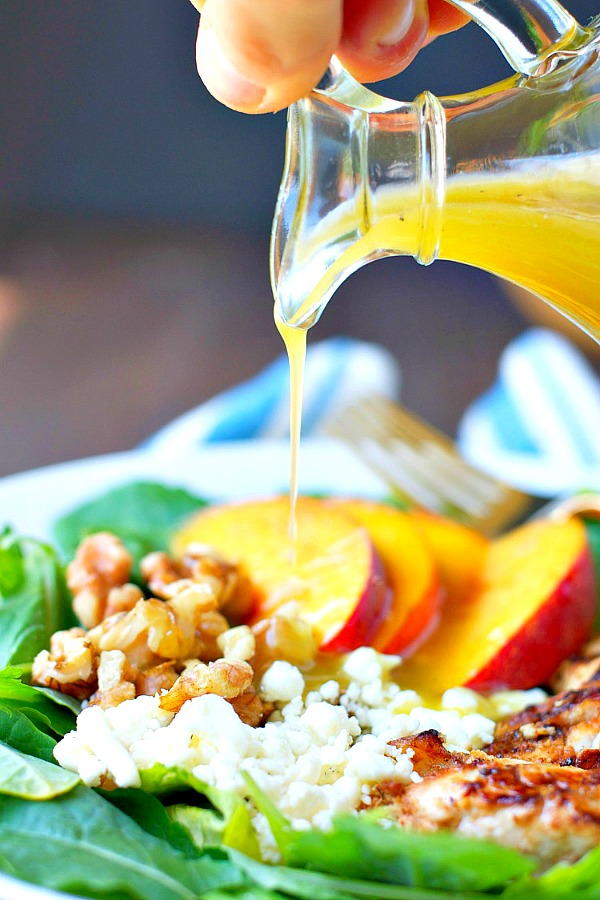 Pouring dressing on grilled chicken salad with fresh nectarines