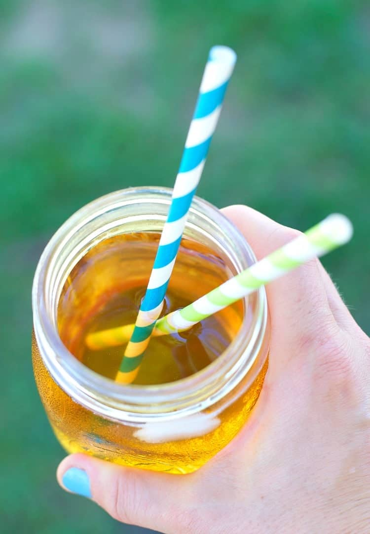 A close up of sweet tea in a glass with two straws