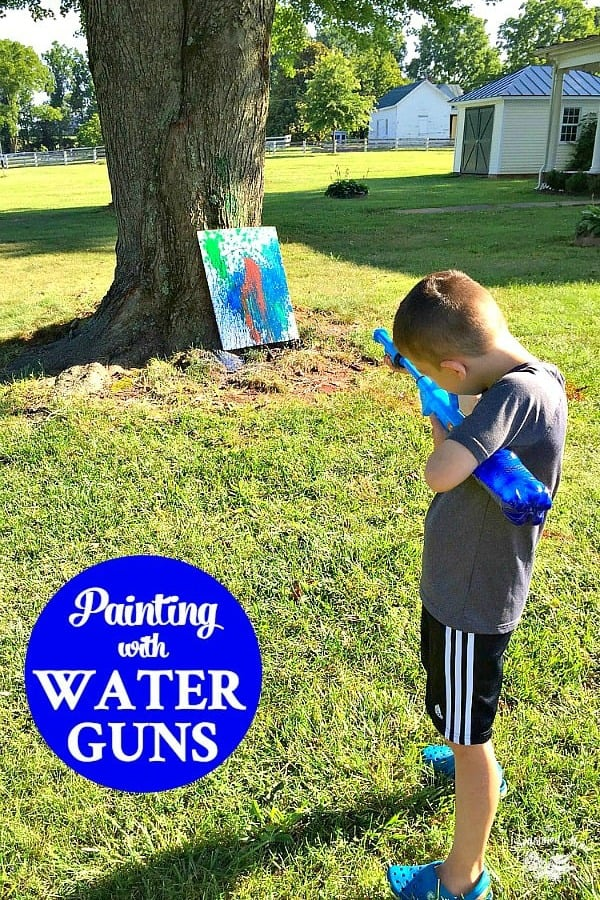 Boy painting with a water gun