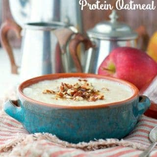 A bowl of protein oatmeal topped with walnuts sitting on a table