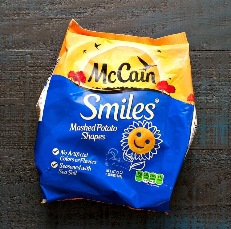 An overhead shot of a packet of Mcains smiles shaped mashed potatoes