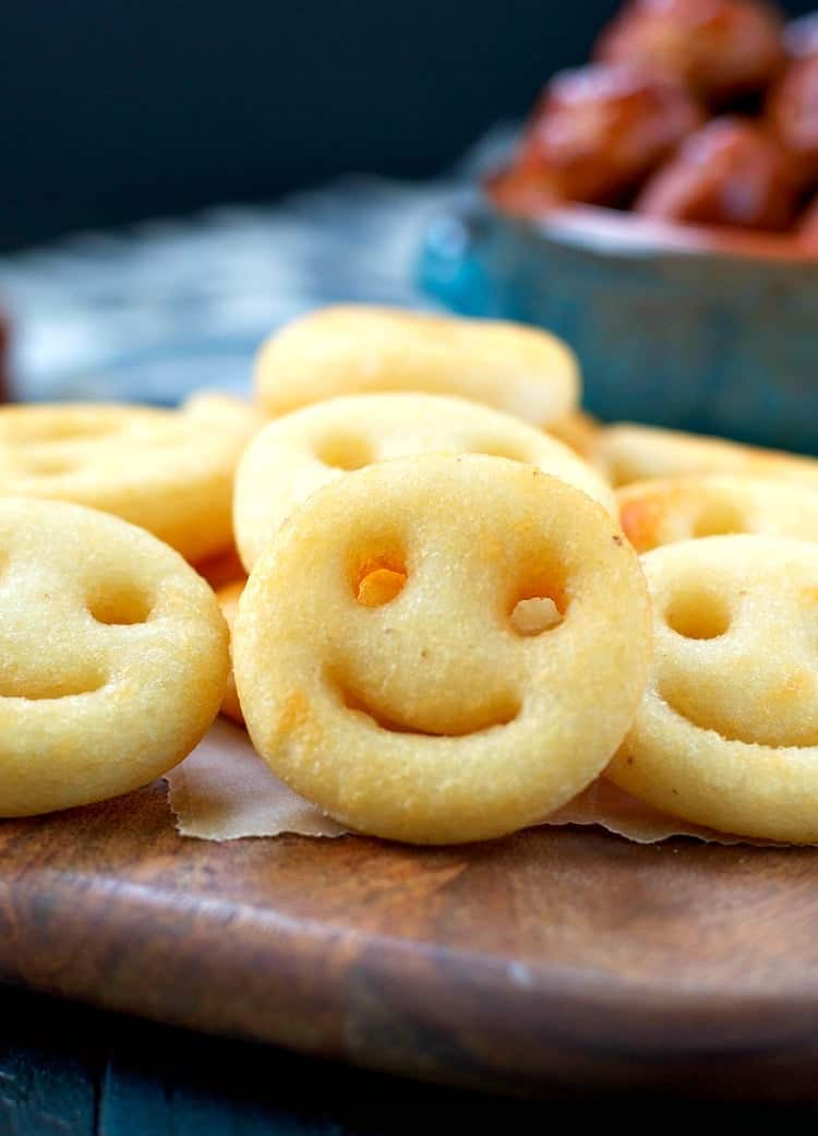 A close up of smiley face potatoes with a bowl of barbecue meatballs in the background