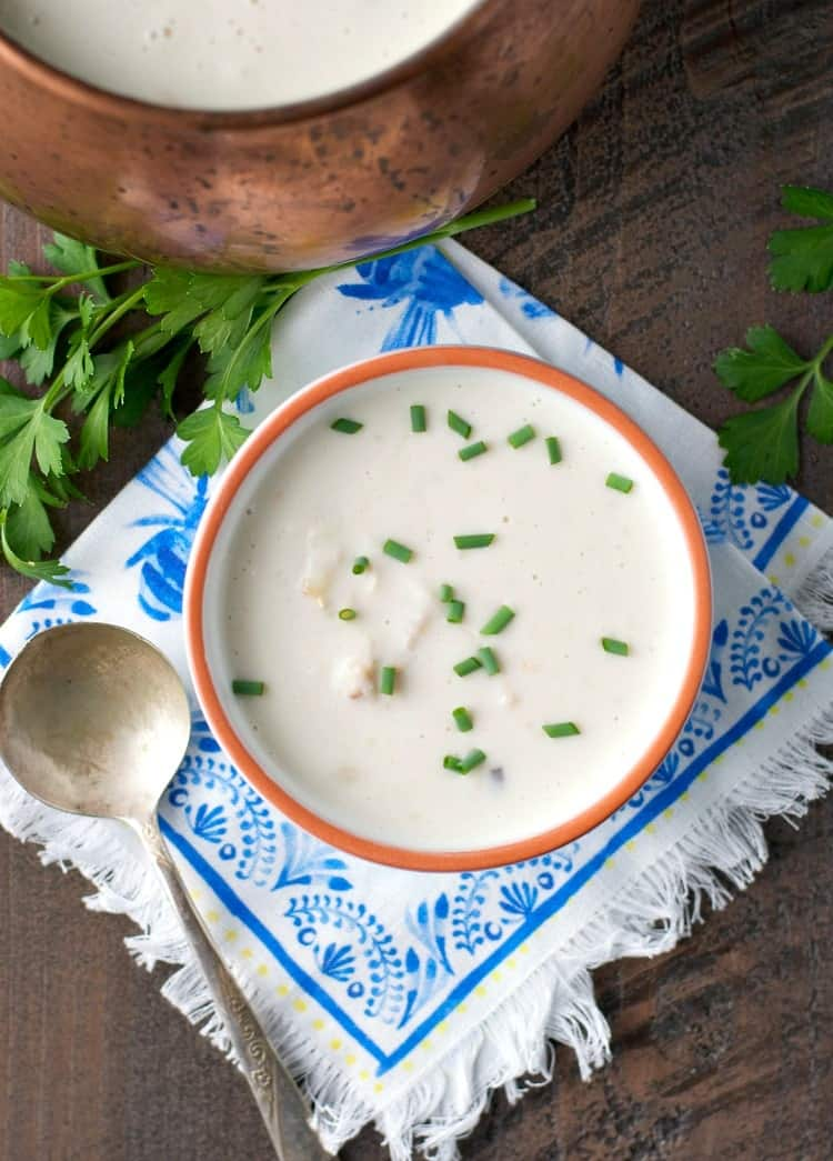 An overhead shot of a crab bisque in a white bowl with a spoon at the side
