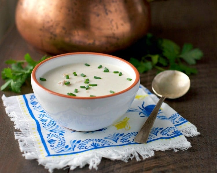 A crab bisque in a white bowl topped chives