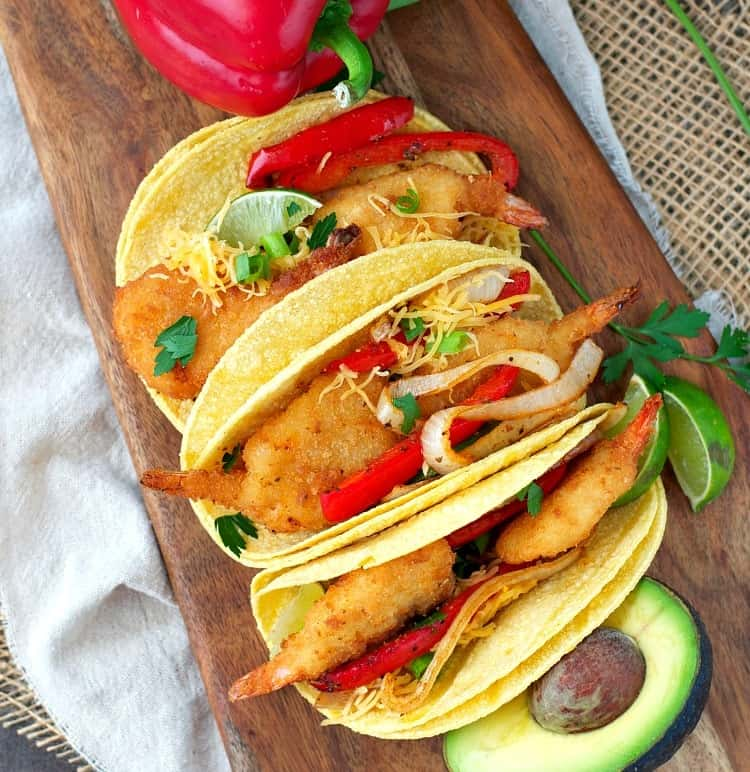 An overhead shot of Crispy Shrimp Fajitas on a wooden board with avocado and sliced bell peppers