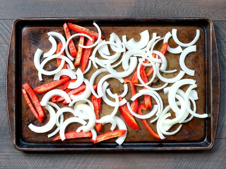 Slices of onion and red bell pepper on a sheet pan for making shrimp fajitas