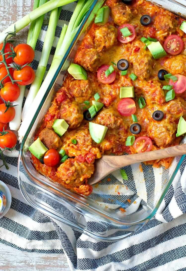 An overhead shot of a taco casserole topped with avocado , tomatoes and olives