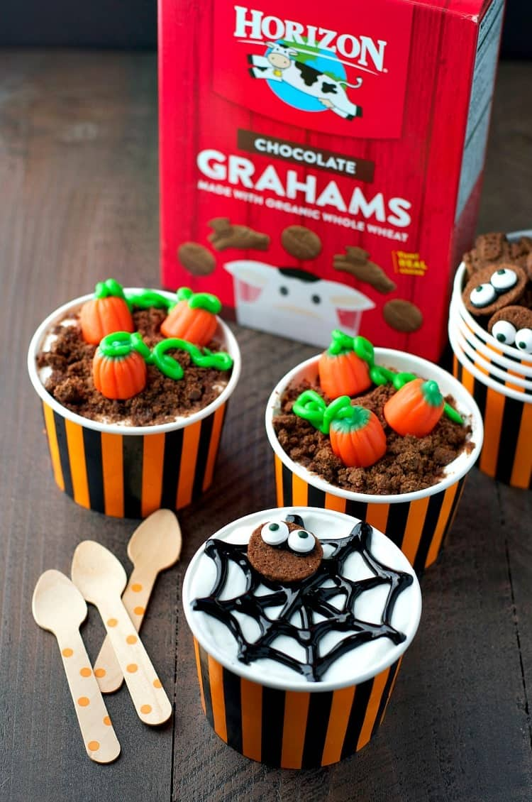 A side shot of Halloween yogurt pots topped with spider web shapes and pumpkin candy