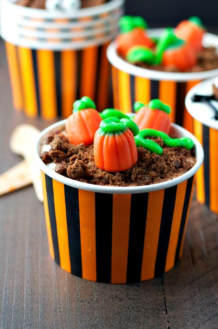 A close up of halloween yogurt cups in orange and black striped cups