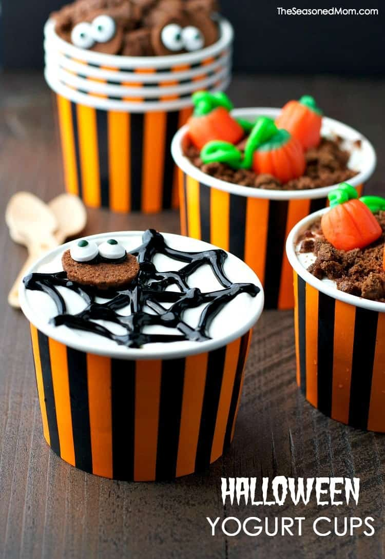 A close up of Halloween yogurt pots sitting on a dark work top