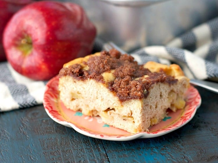 A close up of a slice of apple coffee cake on a small pink plate with apples in the background
