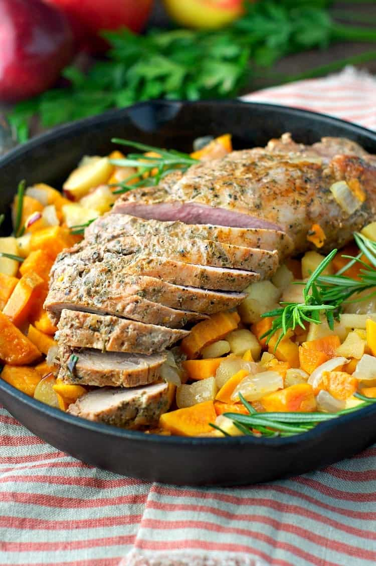 A close up of pork tenderloin with apples in a skillet