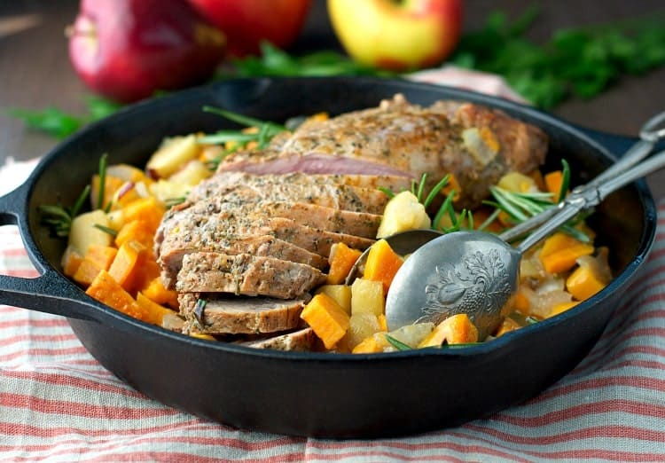 A side shot of pork tenderloin in a skillet with apples and sweet potatoes