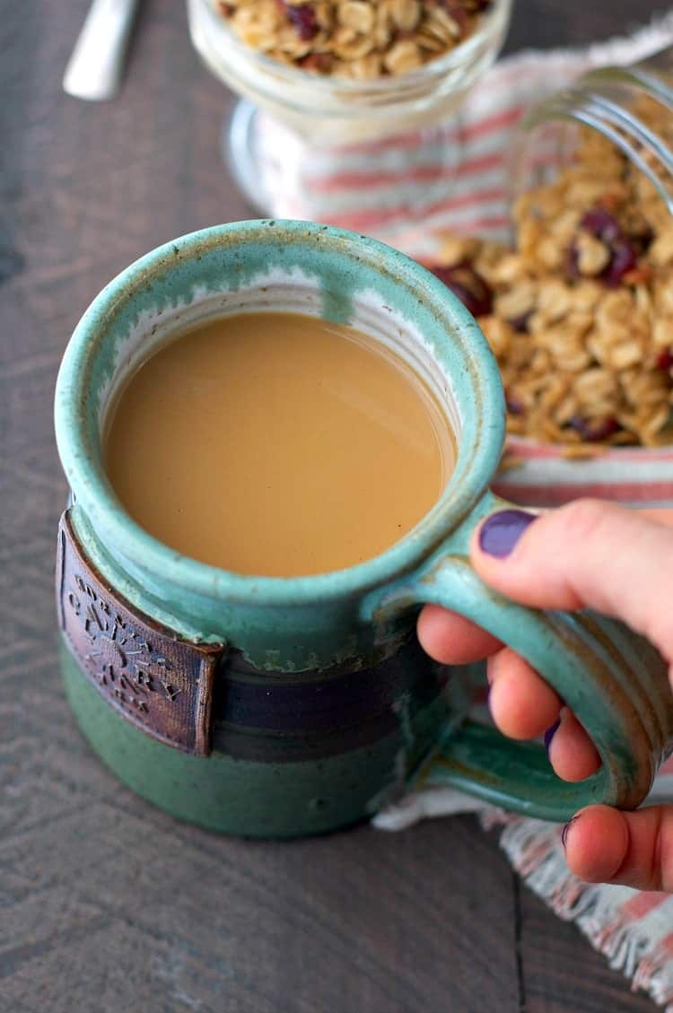 A photo of a mug of coffee with pumpkin spice granola in the background