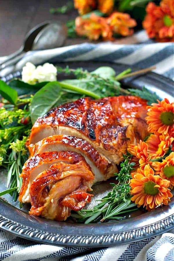 Side shot of an oven roasted turkey breast with flowers and greens surrounding