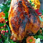 Oven Roasted Turkey Breast with maple glaze served on a silver platter with flowers surrounding