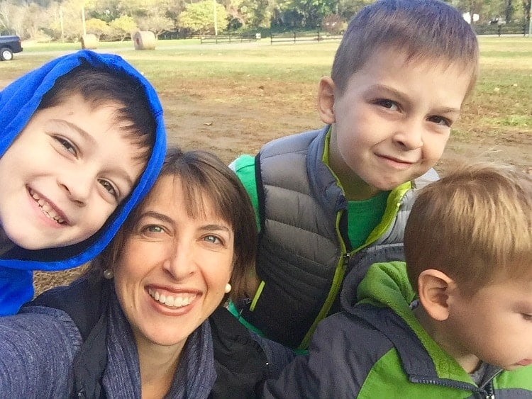 A family photo of four outside at a park