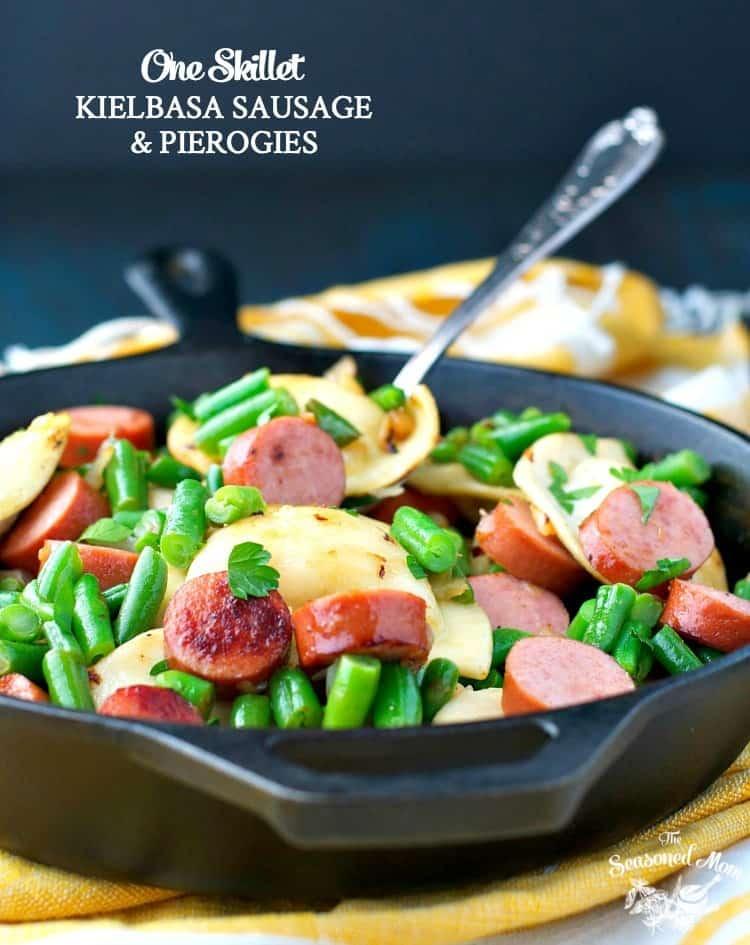 A close up of skillet pan with kielbasa sausage and pierogies