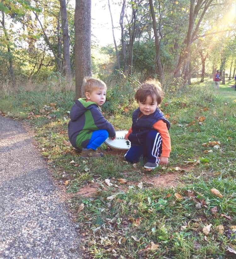 A photo of two boys sitting on grass in a park