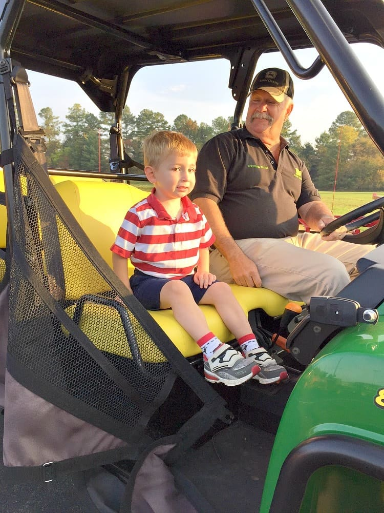 A small boy on a tractor wearing a red and white top