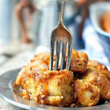Fork digging into Cinnamon Roll Monkey Bread on a small plate