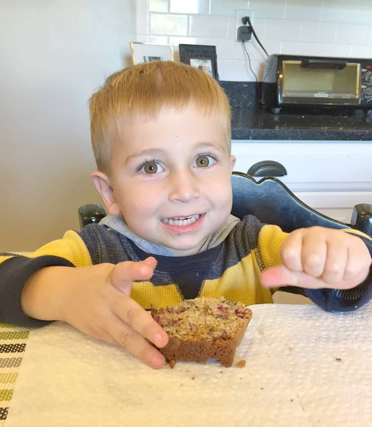 A photo of a boy eating a slice of cranberry bread