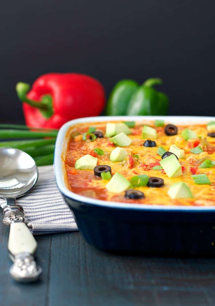 A close up side shot of a chicken fajita bake topped with avocado and olives