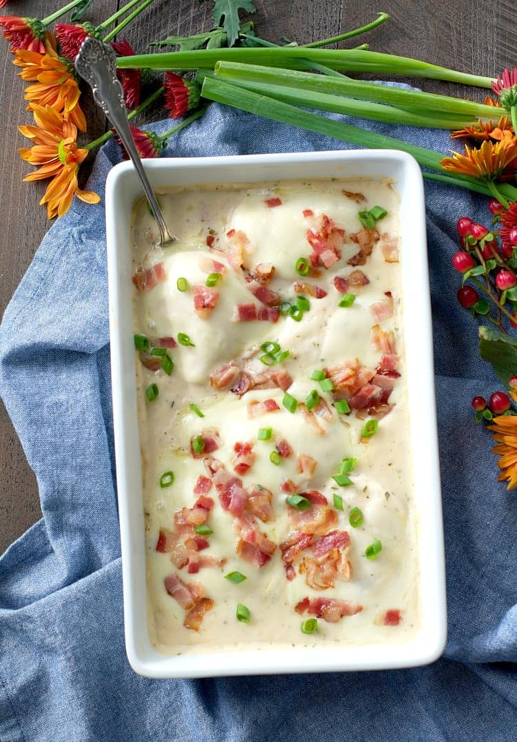 An overhead shot of smothered chicken with bacon in a white casserole dish