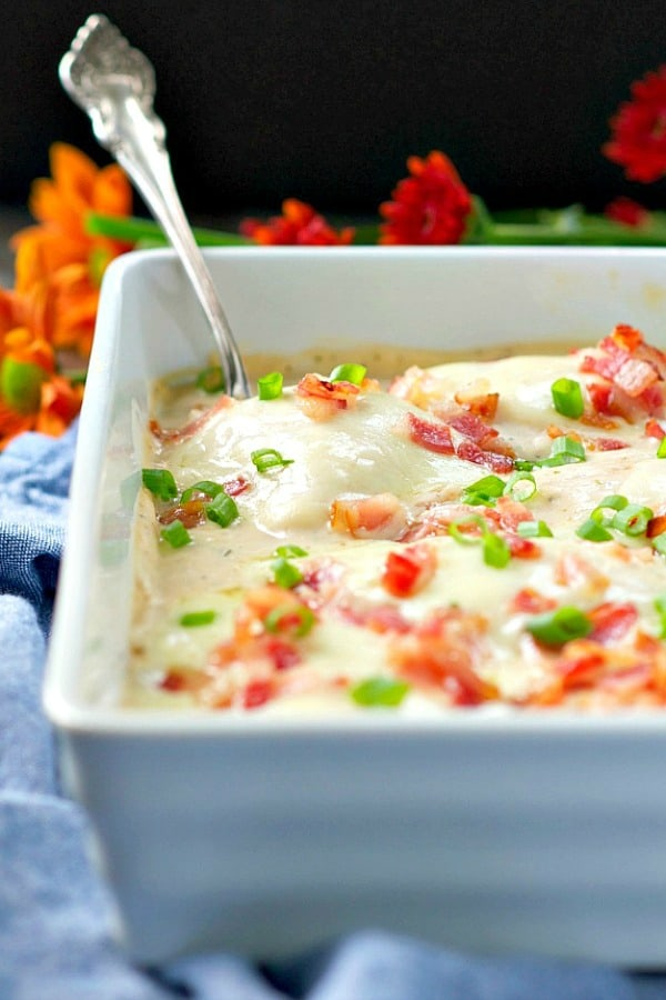 Baked chicken in casserole dish topped with cheese, bacon and green onions