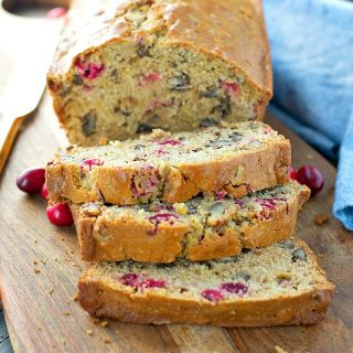 Loaf of sliced cranberry bread on wood cutting board