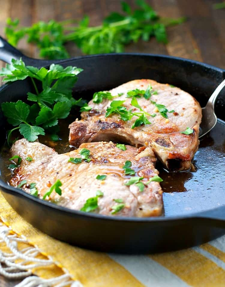 A side shot of brown sugar pork chops in a skillet topped with fresh parsley