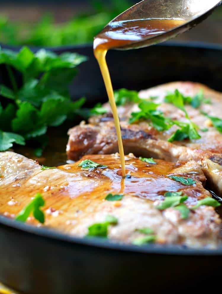 Brown sugar pork chops in a pan with a sauce getting drizzled over them