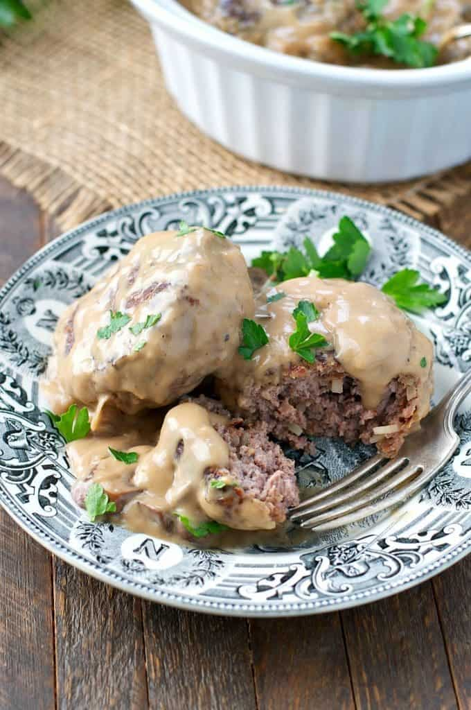 Two pieces of Slow Cooker Salisbury Steak on a plate garnished with parsley