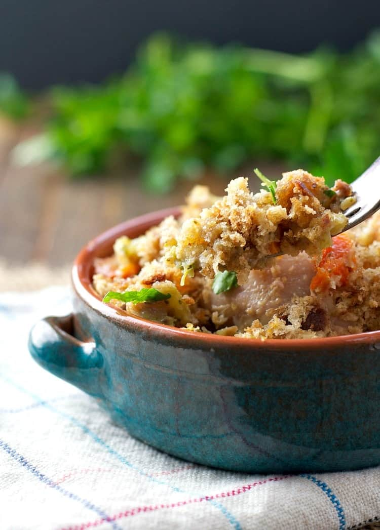 A fork picking up a bite of slow cooker chicken and stuffing casserole from a bowl