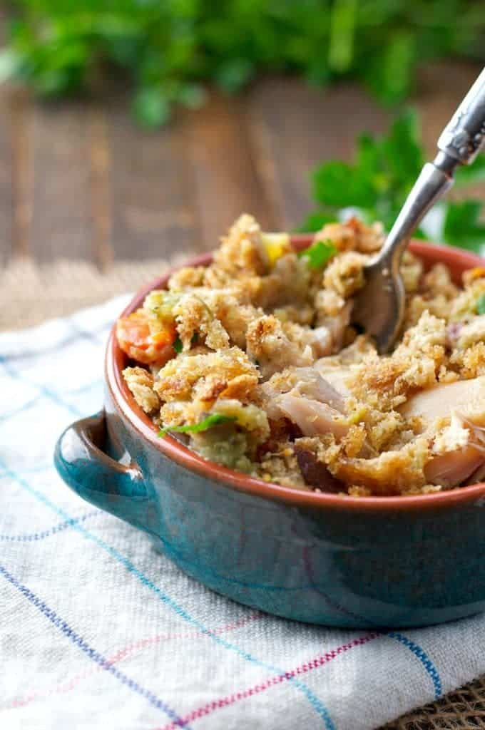 A blue bowl of slow cooker chicken and stuffing casserole with a spoon