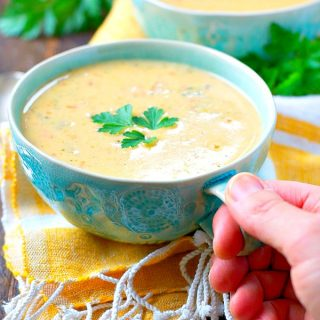 Hand holding cup of broccoli cheese soup with ham