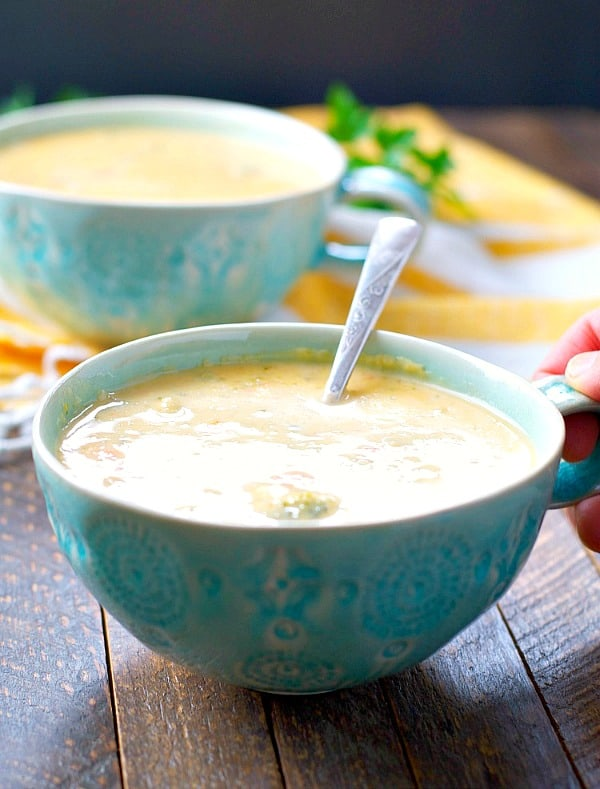 Slow cooker broccoli cheese soup with leftover ham in a blue mug