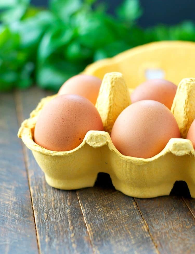 A close up of eggs in a yellow carton used to make egg muffins