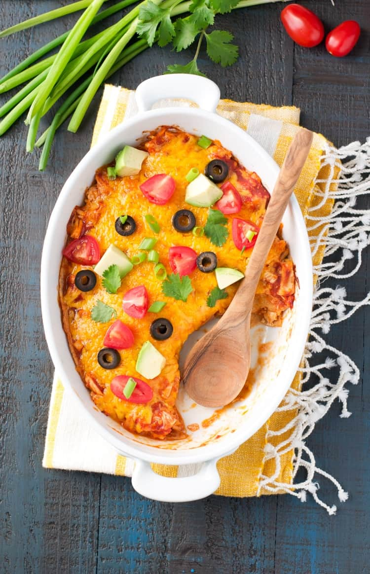A chicken quesadilla casserole in a white dish topped with avocado, tomatoes and olives