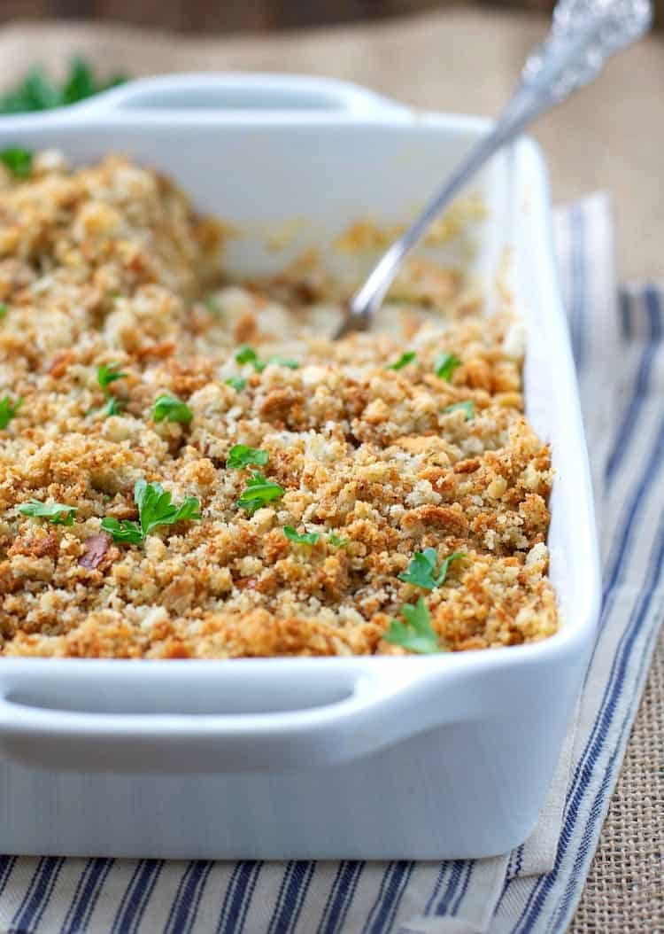 Chicken and Stuffing Casserole in a white casserole dish with a serving spoon