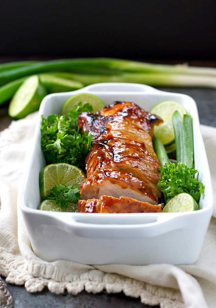 A side shot of a baking dish with hoisin pork and lime wedges