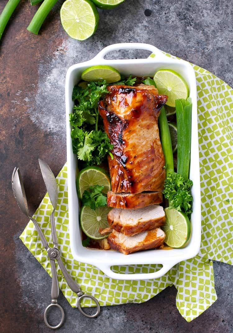 An overhead shot of a hoisin pork loin in a baking dish with lime wedges and herbs