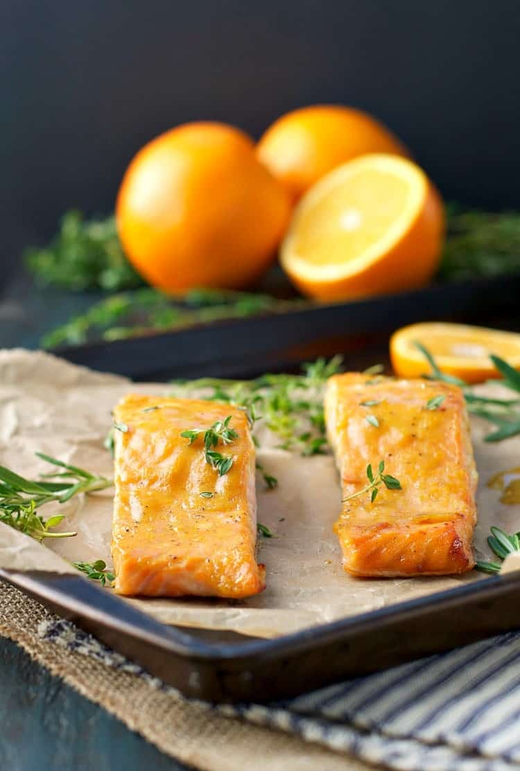 Two fillets of orange maple baked salmon on a sheet pan