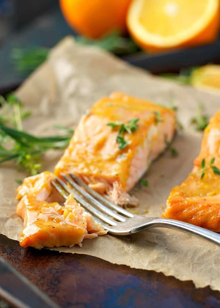 A fillet of orange maple baked salmon with a fork on a sheet pan