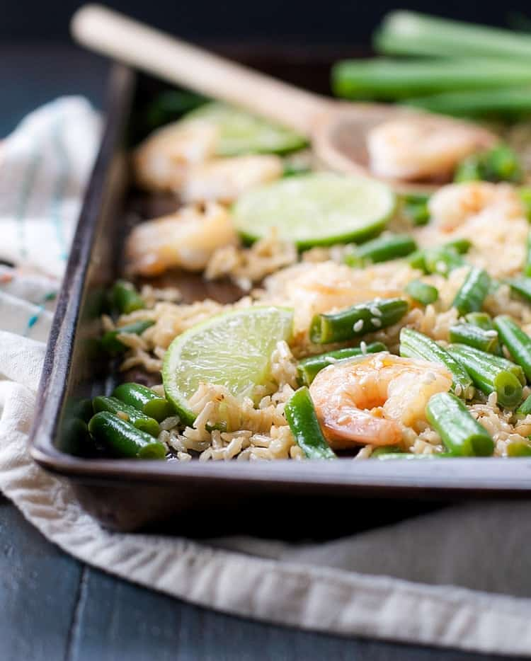 A close up of Honey Garlic Shrimp with Rice and Green Beans on a sheet pan with a slice of lemon