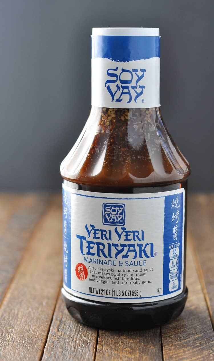 A bottle of teriyaki sauce sitting on a wooden surface