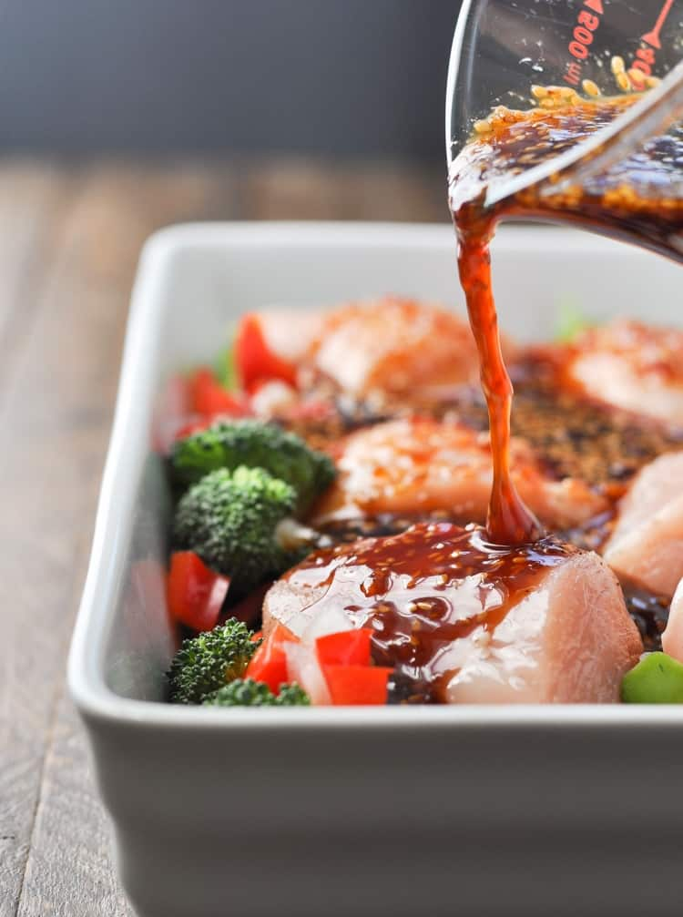 Chicken Teriyaki in a baking dish with someone pouring teriyaki sauce on top