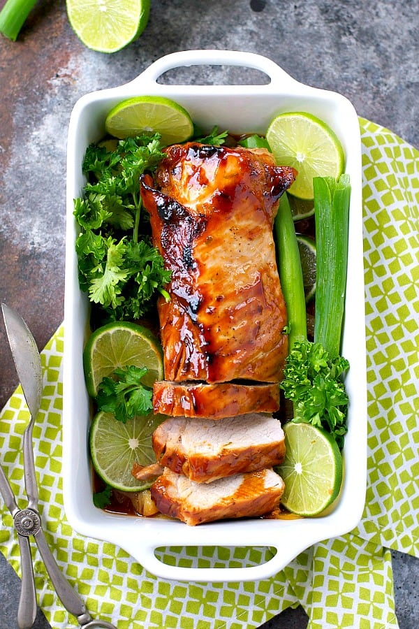 Hoisin Pork Loin surrounded by lime wedges in a white baking dish