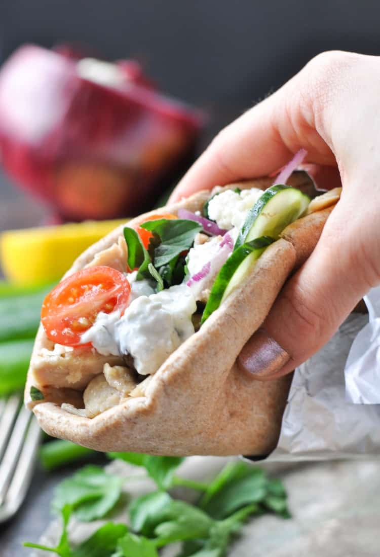 Close up of a hand holding Greek Chicken Gyros