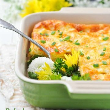 A baked ham and cheese omelet in a baking dish with flowers in the background